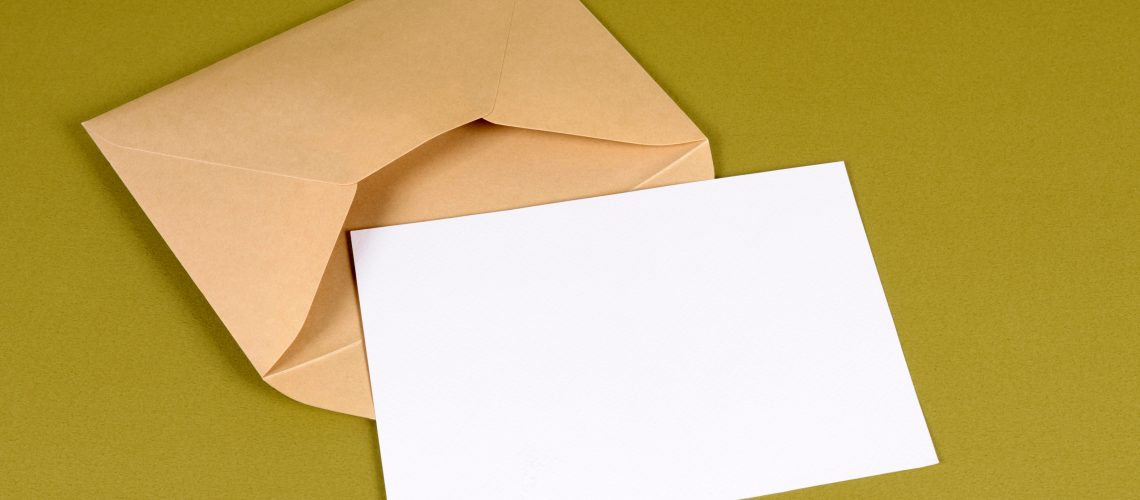 Metallic gold envelope with blank message card letter or invitation isolated on a green background.  Space for copy.