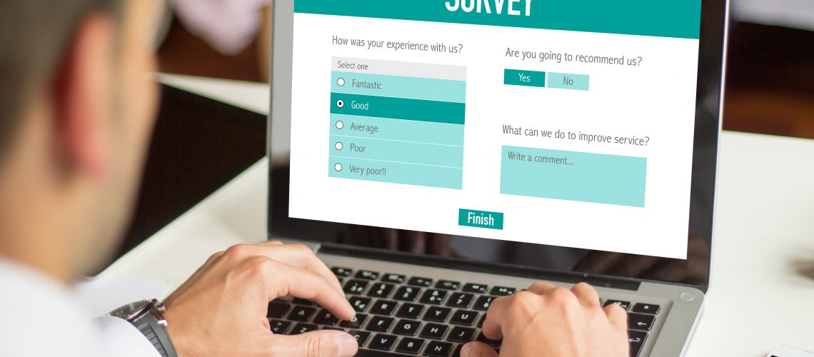 Customer concept: businessman with online survey form on the screen. All graphics on the screen are made up.