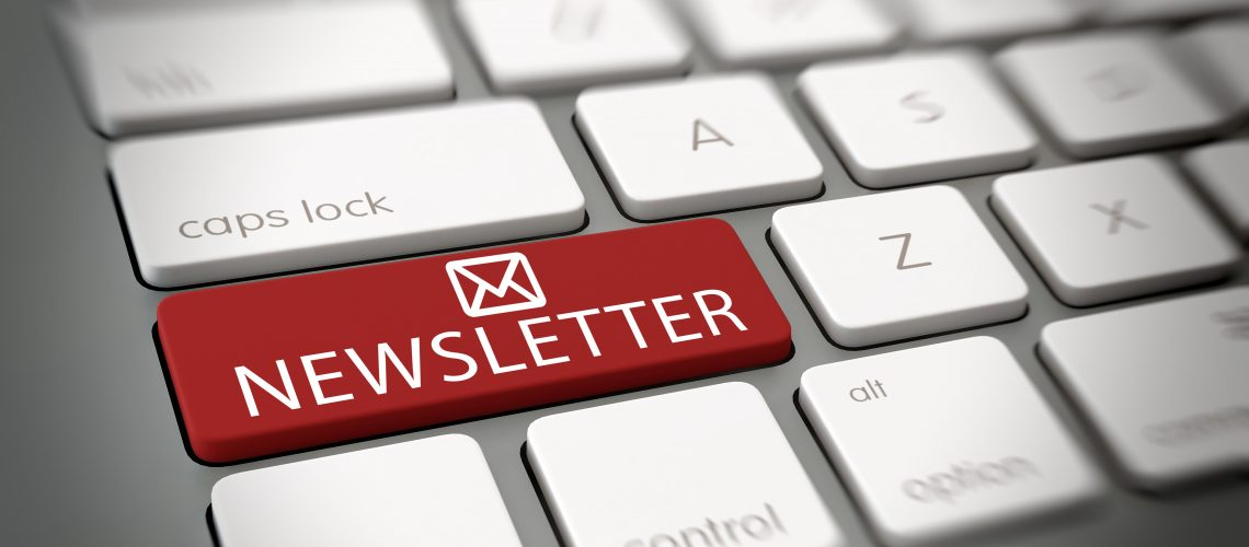 Online newsletter mail concept with a close up angled view of a white computer keyboard with a single large red key with an email or mail icon and the word - Newsletter - in white text