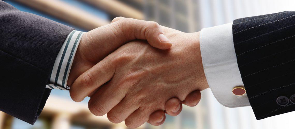business handshake over blue background/apreton de manos sobre fondo azul